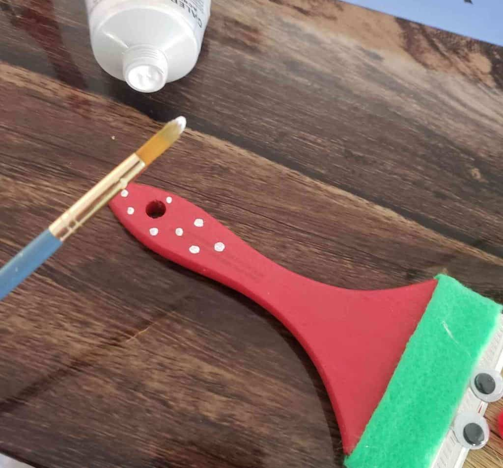 Adding the Polka Dots to the handle of our cute DIY Holiday Paint Brushes