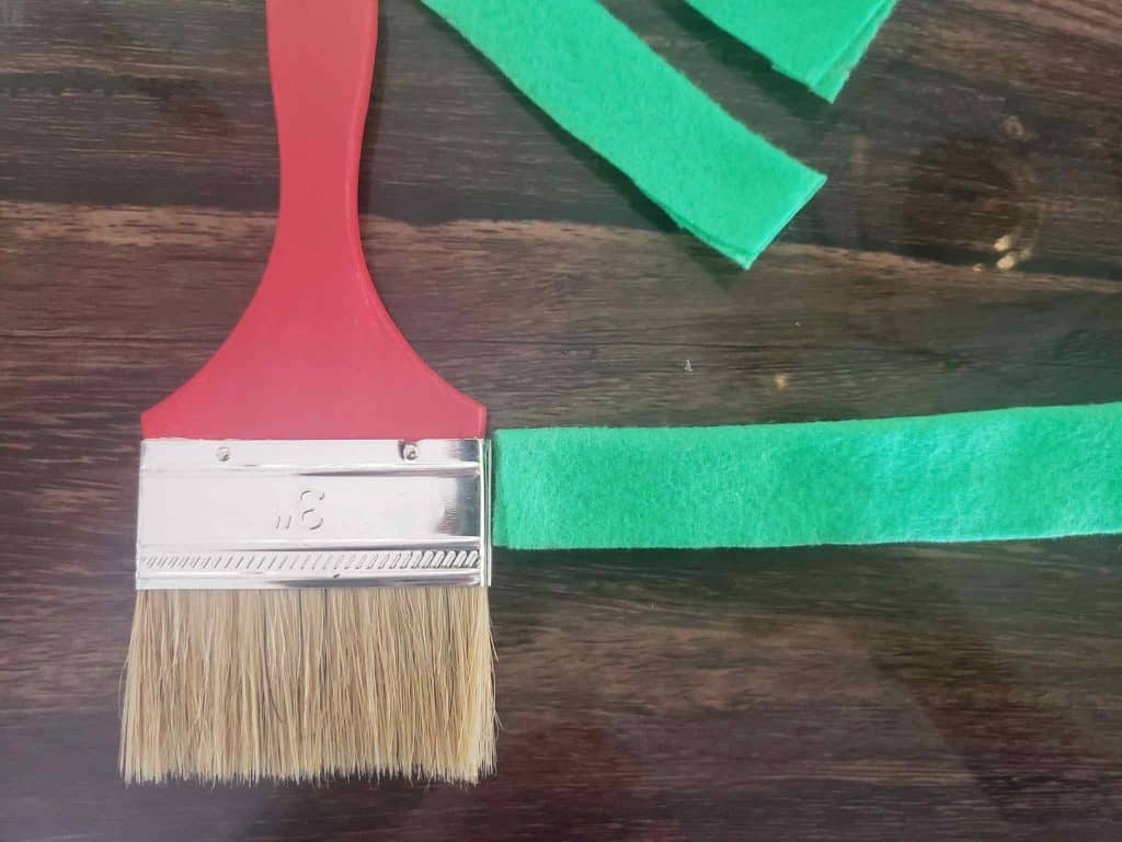 Measuring how thick the felt should be to fit our DIY Holiday Paint Brush